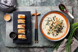 Creamy soup with Eel and sushi rolls on stone slate background