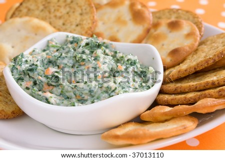 Creamy spinach dip with crackers.