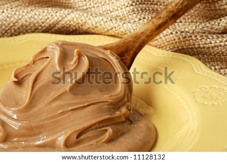 Creamy swirls of peanut butter on a vintage wooden spoon resting on a ceramic plate.  Natural, textured fabric in the background.  Shallow dof with focus on the peanut butter swirls.