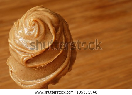 Creamy swirls of peanut butter with color coordinated wood cutting board in background.  Macro with extremely shallow dof.