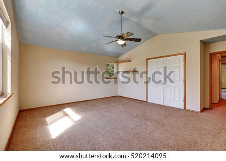 Creamy tones empty room with closet and shelves, vaulted ceiling and carpet floor . Northwest, USA