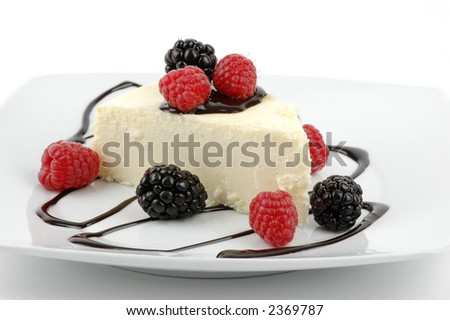Creamy traditional cheesecake with berries and chocolate sauce.