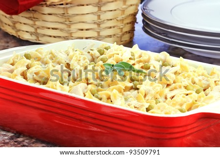 Creamy Tuna and Pasta Dinner with a basket of bread and dinner plates in background. Shallow depth of field. .