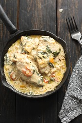 Creamy Tuscan Chicken is a simple but very richly flavoured dish made with chicken cooked and served with a creamy garlic sauce and fresh tomato and spinach. Selective focus