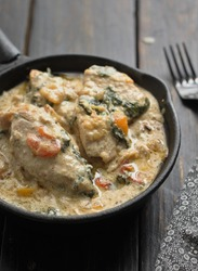 Creamy Tuscan Chicken is a simple but very richly flavoured dish made with chicken cooked and served with a creamy garlic sauce, fresh tomato and spinach. Selective focus