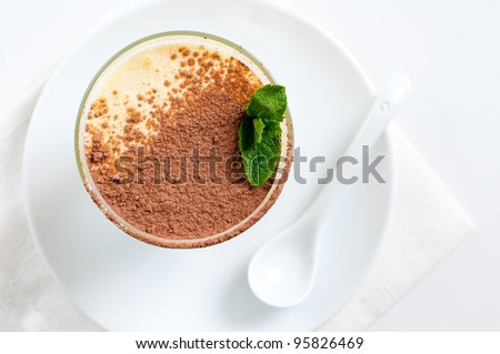 Creamy vanilla dessert with cocoa and mint leaf