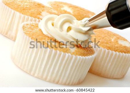 Creamy vanilla frosting being swirled onto individual sized angel food cakes with professional pastry tip.  Macro with shallow dof.