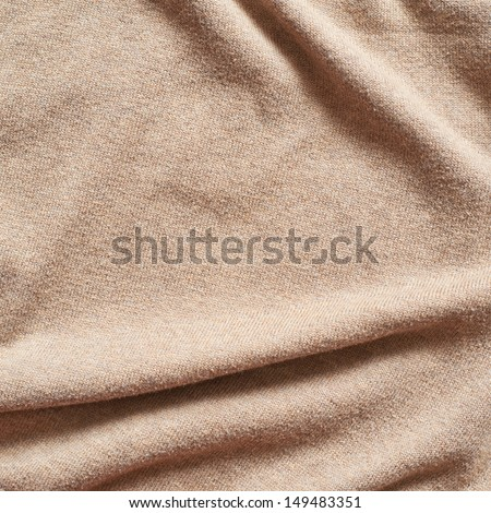 Creased beige cloth material fragment as a background texture