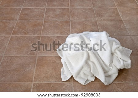 Creased white towels on ceramic floor in a laundry room or bathroom.