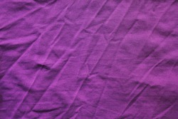 Creasy fabric texture, colorful purple cloth background. Wrinkled worn violet color shirt fragment, close up top view of casual stylish purple shirt