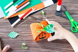 Create a gift box of Halloween pumpkin. The child glues the details of the application of the box. Children's art project, craft for children. Craft for kids.