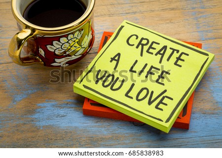 Create a life you love advice or reminder - handwriting in black ink on a sticky note with a cup of coffee