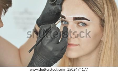 Create permanent eyebrow makeup. Eyebrow dyeing. Face close-up.