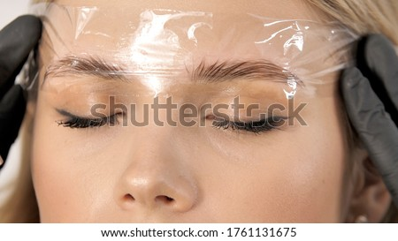 Create permanent eyebrow makeup. Microblading eyebrows work flow in a beauty salon. Cosmetician putting on film on eyebrows. Permanent makeup for eyebrows. Eyebrow lamination and styling  Zdjęcia stock ©