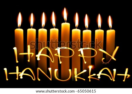 Created by light text Happy Hanukkah and candles over black background
