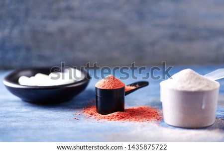 Creatine Powder, Scoop of Whey Protein and Taurine capsules. Sport nutrition. Rustic wooden background. Close up. Copy space