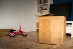 Creating a cardboard playhouse while moving in a new house.
