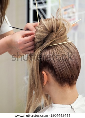 Creating a fashionable female hairstyle in beauty salon.