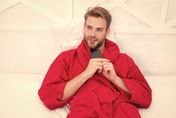 Creating his own blog. Handsome man making new blog post from smartphone. Blogger keeping private personal blog in bed. Caucasian guy in bathrobe posting blog on online social network from bedroom.