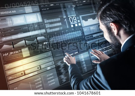 Creating program. Clever excited young programmer feeling confident while standing in front of a convenient transparent screen and creating a new program #1041678601