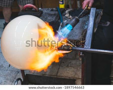 Photo of  Creating traditional glass Art with Hot Torch and glassblowing pipe.  Creating the heavy glass bowl by traditional method
