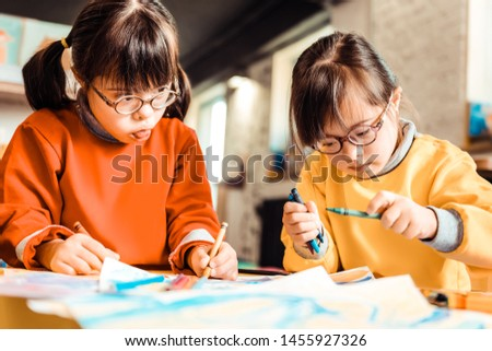 Creating with sister. Little concentrated kids with down syndrome working on a new picture while having developing classes