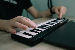 Creation a soundtrack using laptop, midi keyboard and other equipment in home studio. Beat making, arranging audio content, composing song