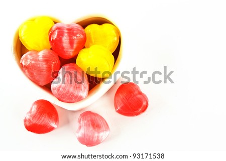 Creation of colorful heart-shaped candies isolated on white background.