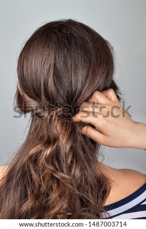 Creation stage of greek style hairdo. Hairdresser doing twist on curly hair