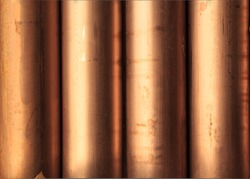 Creative abstract heavy non-ferrous metallurgical industry and industrial manufacturing business production concept: heap of background shiny metal copper pipes with selective focus effect