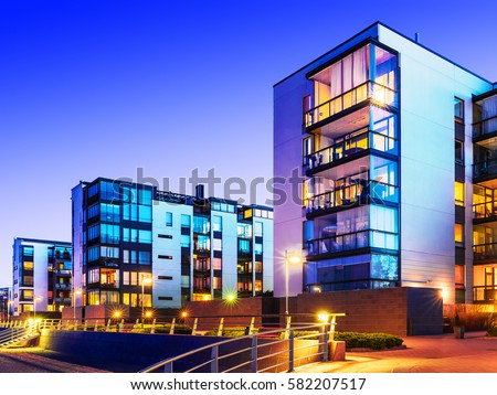 Creative abstract house building and city construction concept: evening outdoor urban view of modern real estate homes #582207517