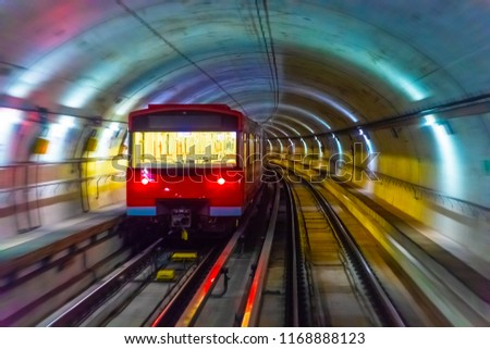 Creative abstract urban city transporation transit technology industrial business concept: red metro train in subway underground tunnel station platform with motion blur effect #1168888123