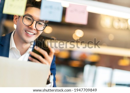 creative agency smart glasses asian male formal cloth conversation with smartphone freelance working with laptop at coworking area office space with freshness with blur office background Foto stock ©