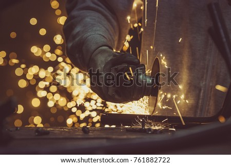 Creative and colored, horizontal image of man working with steel pipe, producing golden sparks on the work surface.