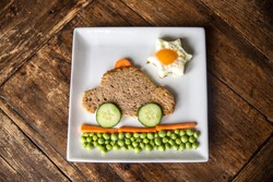 Creative and healthy kids meal, cute taxi car  made from toasted bread, sun from egg and tasty fresh vegetables: carrots, green peas, cucumber.