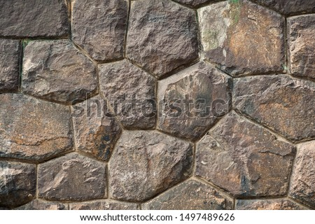 creative art background of large brown stone boulders in an ancient wall with high-precision masonry face to face for an original historical project or artistic design or decor