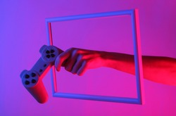 Creative art. Female hand holding retro gamepad through a soaring frame with neon holographic light. Gradient glow. 80s entertainment