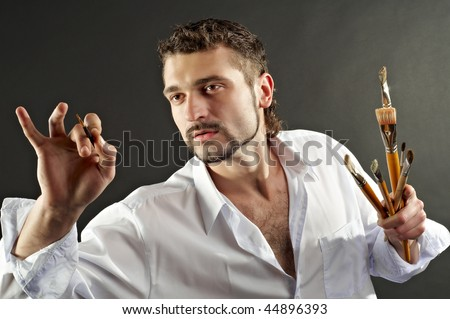 Creative artist in a white shirt on a black background with a brush