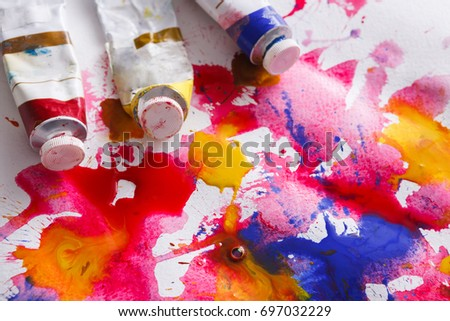 Creative artistic background. Oil-paint tubes on hand painted watercolor. #697032229