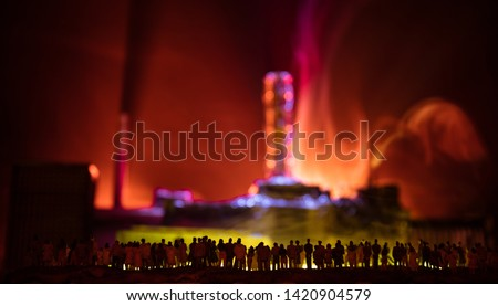 Creative artwork decoration. Chernobyl nuclear power plant at night. Layout of abandoned Chernobyl station after nuclear reactor explosion. Crowd looking on burning reactor. Selective focus