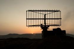 Creative artwork decoration. Silhouette air defence radar antenna during sunset. Satellite dishes or radio antennas against evening sky. Selective focus