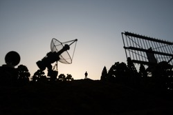 Creative artwork decoration. Silhouette of a man standing near giant air defence radar antenna during sunset. Satellite dishes or radio antennas against evening sky. Selective focus