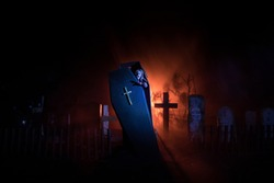Creative artwork. Miniature wooden coffin with zombie inside. Scary view of zombies at cemetery. Horror Halloween concept. Selective focus