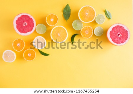 Creative background made of summer tropical fruits with leaves, grapefruit, orange, tangerine, lemon, lime on pastel yellow background. Food concept. Flat lay, top view, copy space #1167455254