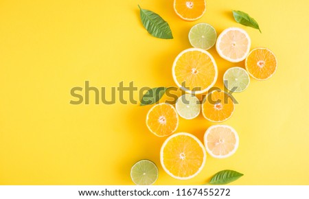 Creative background made of summer tropical fruits with leaves, grapefruit, orange, tangerine, lemon, lime on pastel yellow background. Food concept. Flat lay, top view, copy space #1167455272