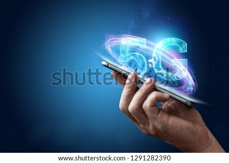 Creative background, male hand holding a phone with a 5G hologram on the background of the city. The concept of 5G network, high-speed mobile Internet, new generation networks. Mixed media.