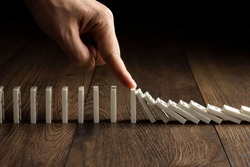 Creative background, Men's hand stopped domino effect, on a brown wooden background. Concept of domino effect, chain reaction, risk management, copy space.
