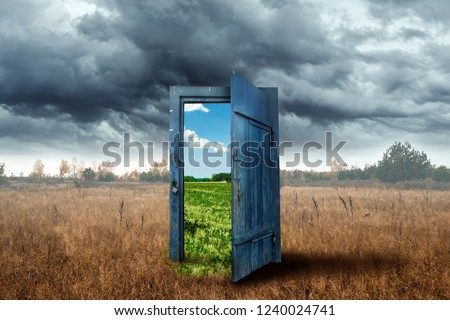 Photo of  Creative background. Old wooden door, blue color, in the box. Transition to a different climate. The concept of climate change, portal, magic. Copy space.