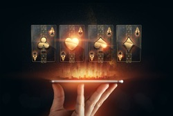 Creative background, online casino, in the male hand a smartphone with playing cards, black-gold background. Internet gambling concept. Copy space
