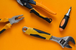 Creative background with hand tools. Hand tool with black and orange handles on an orange background. Pliers, screwdriver, adjustable wrench and scissors for cutting metal. View from above.